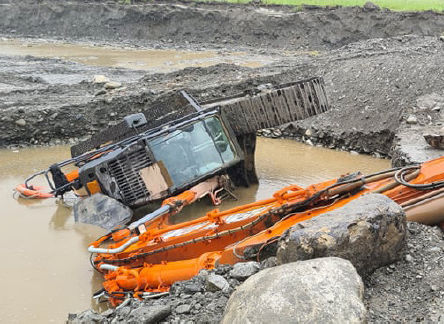 [Image] Orange excavator tipped over in mine pond.
