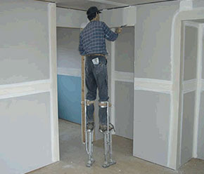 [image] A plasterer uses stilts to comfortably reach above door frames